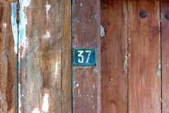 Old metal number 37 plaque on a old wooden door. An Old metal number 37 plaque on a old wooden door Royalty Free Stock Photos