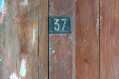 Old metal number 37 plaque on a old wooden door. Stock Photo