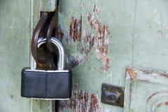 Old metal padlock on old painted wooden door Royalty Free Stock Photos