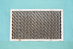 Old metal patterned ventilation grid on the plastered wall Stock Image
