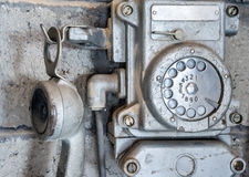 Old a metal phone on wall. Old a metal telephone with a turning circle for dialing number on wall closeup Royalty Free Stock Image