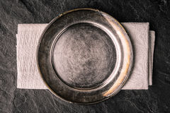 Old metal plate on the dark stone table top view Royalty Free Stock Images
