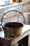 Old metal pot on wooden table Stock Photo