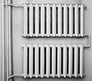 Old metal radiators on wall. Old and dirty metal radiators. Monochrome for additional feel on their age Stock Images