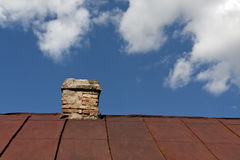 Old metal roof with brick chimney against cloudy sky. Stock Photography