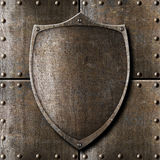 Old metal shield over armour background. With rivets Stock Image
