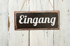 Old metal sign in front of a white wooden wall - German word for Entrance - Eingang stock image