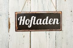 Old metal sign in front of a white wooden wall - German word for Farm Shop - Hofladen stock photos