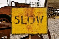 An old metal sign with the Word SLOW. A very old rusty tin sign encourage to drive or move slowly royalty free stock photo