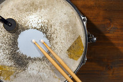 Old Metal Snare Drum with Drumsticks. Close up of metallic and old snare drum with wooden drumsticks on dark wooden background royalty free stock photography