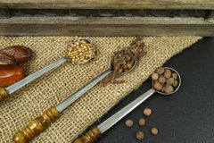 3 old metal spoons with spices on burlap background Stock Photo