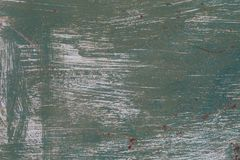 Old metal surface painted with green paint with strokes of white paint.  stock photography