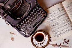 Old metal typewriter, covered in dust and rust.Cup of coffee on the table. The atmosphere of comfort and creativity. Old metal typewriter, covered in dust and Royalty Free Stock Photos