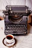 Old metal typewriter, covered in dust and rust.Cup of coffee on the table. The atmosphere of comfort and creativity. Old metal typewriter, covered in dust and Stock Photo