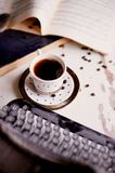 Old metal typewriter, covered in dust and rust.Cup of coffee on the table. The atmosphere of comfort and creativity. Old metal typewriter, covered in dust and Royalty Free Stock Images