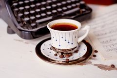 Old metal typewriter, covered in dust and rust.Cup of coffee on the table. The atmosphere of comfort and creativity. Old metal typewriter, covered in dust and Royalty Free Stock Photo