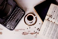 Old metal typewriter, covered in dust and rust.Cup of coffee on the table. The atmosphere of comfort and creativity. Old metal typewriter, covered in dust and Stock Photos
