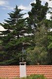Old metal weather vane. On the orange roof royalty free stock photo