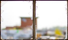 Old metal window frame, broken window glass with blurred view outside stock images