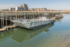 Old metallic ferry boat docked at old wooden pier Stock Photography