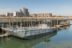 Old metallic ferry boat docked at old wooden pier Royalty Free Stock Photos