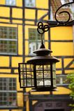 An old metallic lantern hanging from a yellow brick wall in Copenhagen, Denmark stock photos