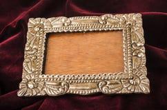 Old metallic photo frame. Old metallic silver photo frame over red velvet textile Royalty Free Stock Photo