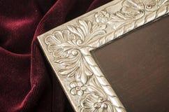 Old metallic photo frame. Old metallic silver photo frame over red velvet textile Royalty Free Stock Image