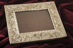 Old metallic photo frame. Old metallic silver photo frame over red velvet textile Stock Photos
