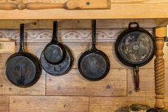 Old metallic rustic pans hanging on the wooden wall. Front view of metal pans Stock Photo