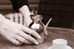 Old metallic  teapot in woman's hands Royalty Free Stock Photos
