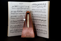 Old metronome with sheet music Royalty Free Stock Photography