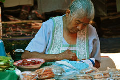 Old Mexican Woman Sewing. Old Woman in traditional laced apron sewing while waiting for buyers at a mexican market Royalty Free Stock Images