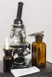 Old microscope and two dark bottles Stock Photos
