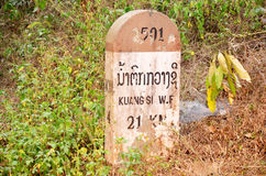 Old Milestone on the road information distance to Kuang Si Falls Stock Images