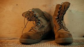 Old military boots on a wooden table. Old brown military boots on a bright wooden table made of boards stock video