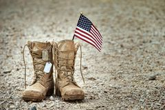Old military combat boots with dog tags and a small American flag