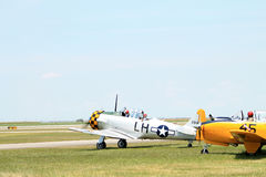 Old military planes on field. Old aircraft in a row on field including US Navy yellow 1957 Beech D-45 (T-34 Mentor), 1944 AT6-D aka the Texan, 2014 Memorial Day Royalty Free Stock Photo