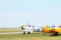 Old military planes on field. Old aircraft in a row on field including US Navy yellow 1957 Beech D-45 (T-34 Mentor), 1944 AT6-D aka the Texan,  2014 Memorial Day Royalty Free Stock Images