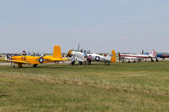Old military planes on field. Old aircraft in a row on field including US Navy yellow 1957 Beech D-45 (T-34 Mentor), 1944 AT6-D, Soviet Yakovlev Yak-52 (Як-52 Royalty Free Stock Photos