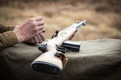Old military rifle. Next to the rifle soldier`s hand stock image
