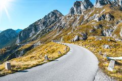 Old military road headed to Mangart saddle high in Julian alps on a sunny beautiful autumn day. With colorful scenery and surrounded with mountain peaks royalty free stock photos