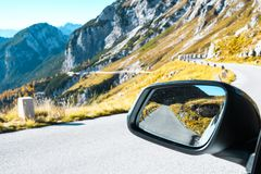 Old military road headed to Mangart saddle high in Julian alps on a sunny beautiful autumn day. With colorful scenery and reflection in a car rear mirror royalty free stock photos
