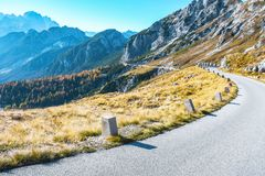 Old military road headed to Mangart saddle high in Julian alps on a sunny beautiful autumn day. With colorful scenery and surrounded with mountain peaks stock image