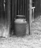 Old Milk Can. Black and white of an old milk can against an old wooden building stock image