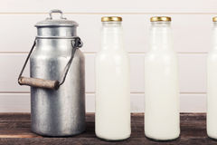 Old milk can and bottles on wooden table royalty free stock photography