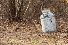 Old milk can laying in wooded area. Royalty Free Stock Photography