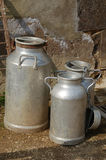 Old milk churns. Three old and rustic metal milk churns Stock Images
