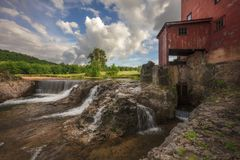 Old Mill along river and waterfall. Old mill sitting next to a waterfall along the river Royalty Free Stock Image