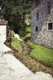 Old mill and an ancient house in the mountains. An old mill close to the ancient house in a landscape image Royalty Free Stock Photography